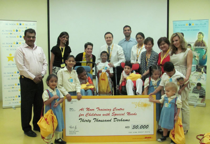 DHL Express staff with children and staff from the Al Noor Centre