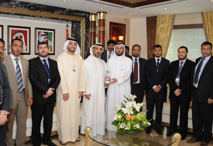 Ahmed Madani presenting the award to HE Ahmed Butti Ahmed with attending officials either side