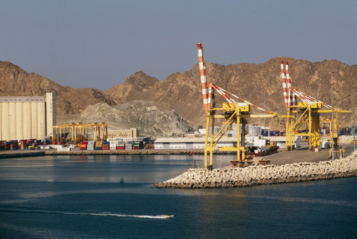 Heavy cranes are seen at the dock under sunlight